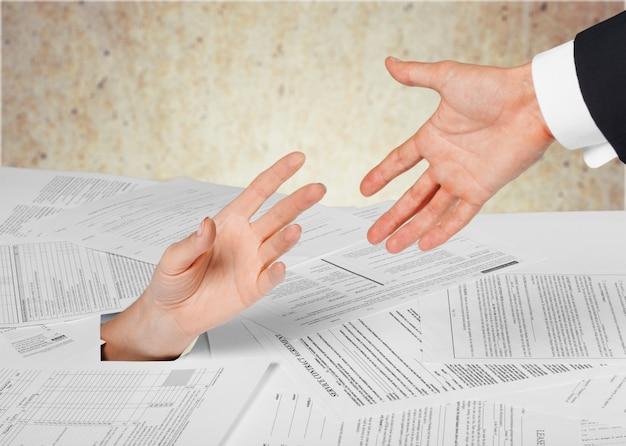 Zbliżenie dłoni bizneswoman w stosie papierów