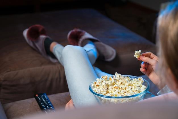Zbliżenie dłoni budząc popcorn z miski podczas oglądania telewizji. osoba siedząca na wygodnej kanapie i oglądająca kino domowe w ciemności.