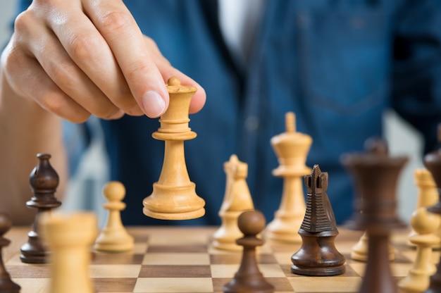 Zbliżenie dłoni człowieka grającego w szachy królowej gospodarstwa
