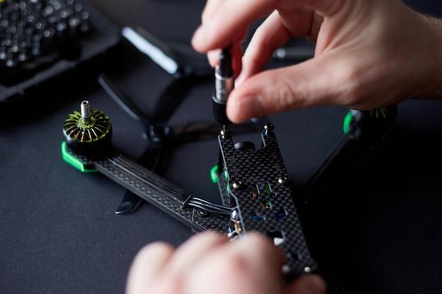 Zbliżenie dłoni człowieka, montaż drona fpv z części, przy użyciu narzędzi, przygotowanie szybkiego quadkoptera wyścigowego do lotu. napraw drona przed treningiem.