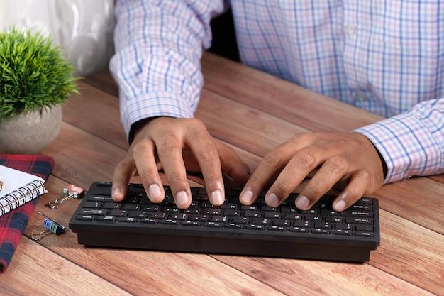 Zbliżenie dłoni człowieka pisania na klawiaturze.