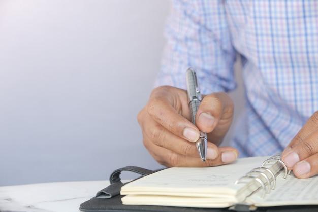 Zbliżenie dłoni człowieka pisania w notatniku.