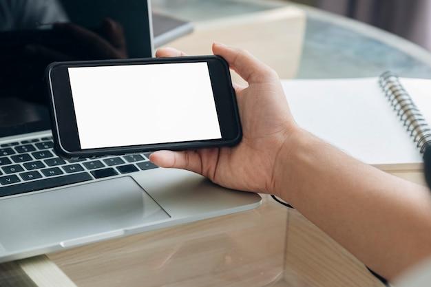 Zbliżenie dłoni człowieka trzymającego inteligentny telefon.