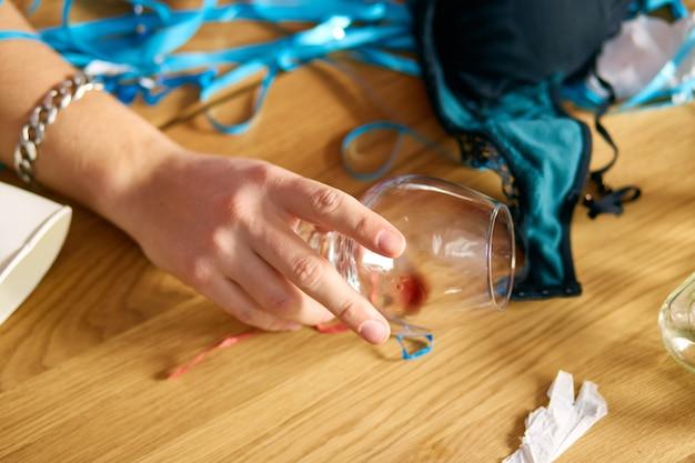 Zbliżenie dłoni człowieka trzymającego kieliszek brandy, śpiącego przy stole w niechlujnym pokoju po wieczorze kawalerskim, zmęczony mężczyzna po imprezie w domu