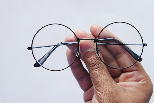 Zbliżenie dłoni człowieka trzymającego stare okulary