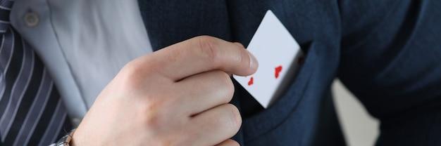 Zbliżenie dłoni człowieka, wyciągając kartę asa z kieszeni koloru