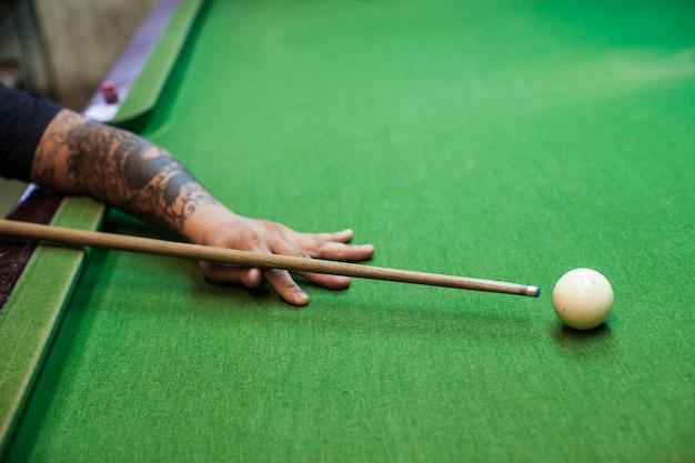 Zbliżenie dłoni człowieka z kijem bilardowym gotowy do trafienia białą piłkę