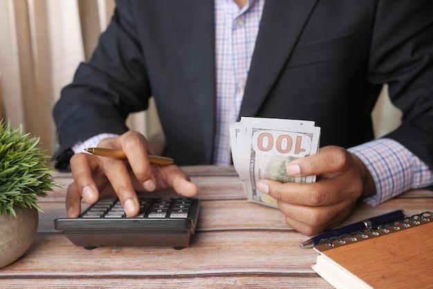 Zbliżenie dłoni człowieka za pomocą kalkulatora i trzymającego dolara