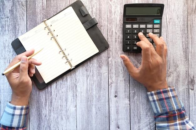 Zbliżenie dłoni człowieka za pomocą kalkulatora