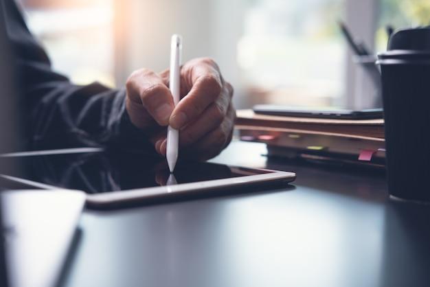 Zbliżenie dłoni człowieka za pomocą pióra z ekranem dotykowym na cyfrowym tablecie na stole w biurze