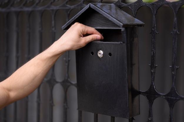 Zbliżenie dłoni dotykając skrzynki pocztowej