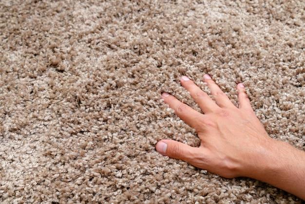 Zbliżenie dłoni dotykającej miękkiego dywanu. delikatny i puszysty dywan.