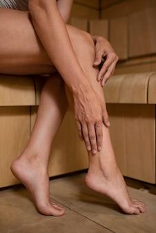 Zbliżenie dłoni dotykających nóg