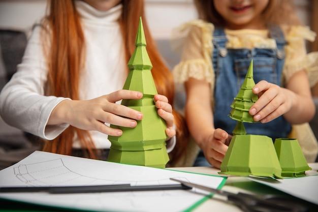 Zbliżenie dłoni dwójki małych dzieci, dziewczynek razem w kreatywności domu. dzieci robią ręcznie robione zabawki do gier lub obchodów nowego roku. małe modele kaukaskie. szczęśliwe dzieciństwo, boże narodzenie.