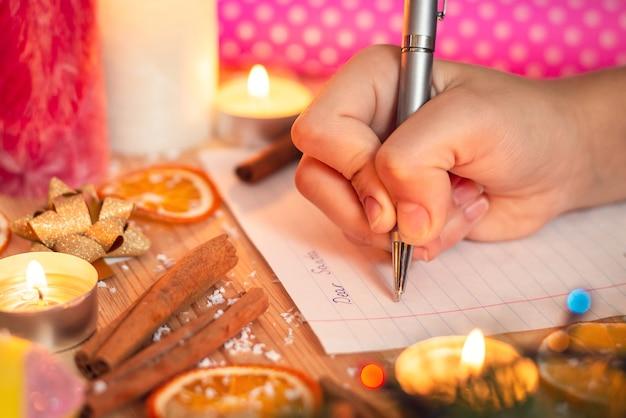 Zbliżenie dłoni dziecka, pisząc list do świętego mikołaja