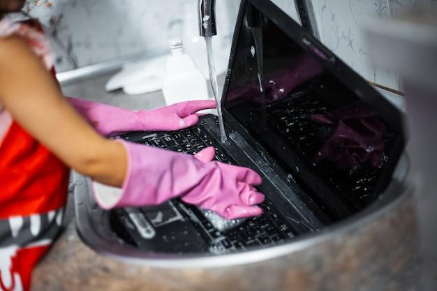 Zbliżenie dłoni dziecka z różowymi rękawiczkami myje laptopa w zlewie w kuchni.
