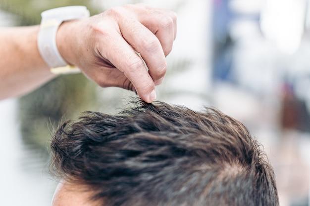 Zbliżenie dłoni fryzjera naprawiającego włosy kaukaskiego klienta żelem do włosów