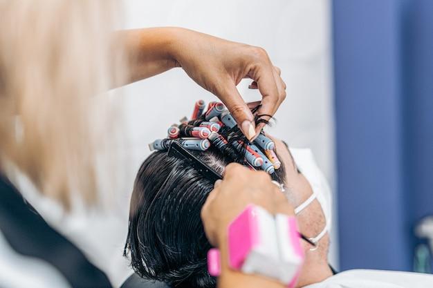 Zbliżenie dłoni fryzjera zwijającego włosy mężczyzny z wałkami podczas noszenia maski