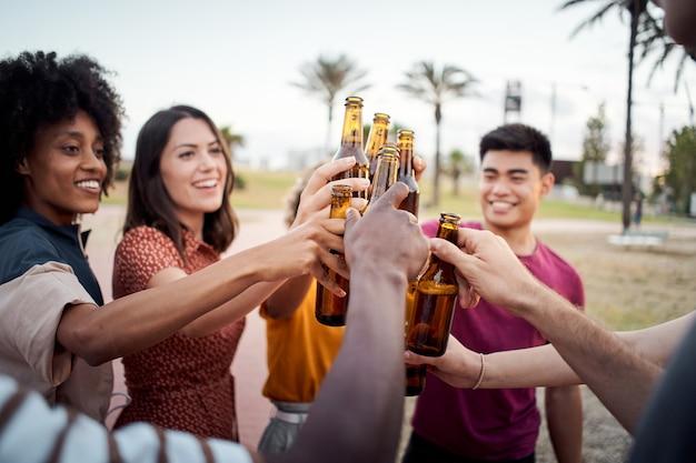 Zbliżenie dłoni grupy młodych ludzi różnych ras wznoszących toast szczęśliwie na okrzyki słońca