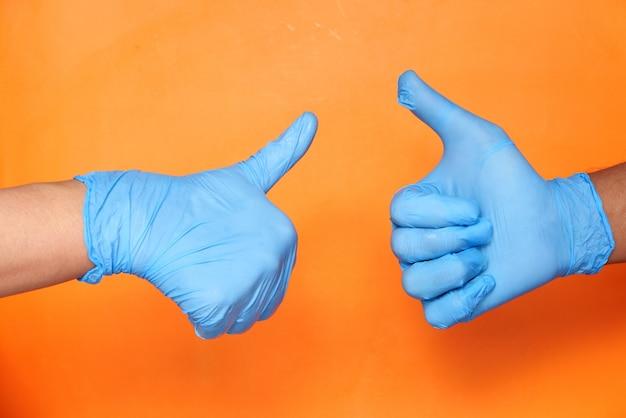 Zbliżenie dłoni holowania ludzi w rękawiczkach medycznych pokazujących kciuk do góry.