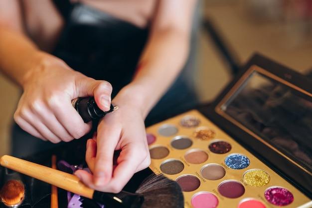 Zbliżenie dłoni i korektor do makijażu. zbliżenie kosmetyków, cieni do powiek, pędzli.