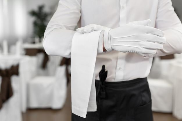 Zbliżenie dłoni kelnera z ręcznikiem.