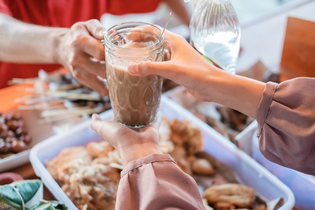 Zbliżenie dłoni kelnerki stoiska kobiet, podając szklankę napoju klientowi w sklepie