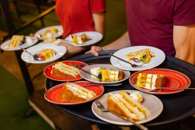 Zbliżenie dłoni kelnerki trzymającej białe talerze z pociętymi kawałkami ciasta. kelner serwuje desery.