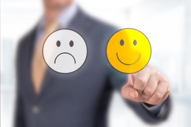 Zbliżenie dłoni klienta wybierz ikonę buźki ocena usług ręka biznesmena wskazująca na optymizm