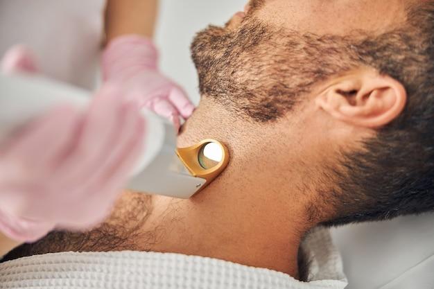 Zbliżenie dłoni kobiecych estetyków w sterylnych rękawiczkach usuwających niechciane włosy z męskiej szyi za pomocą urządzenia laserowego