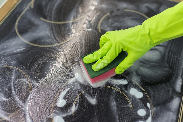 Zbliżenie dłoni kobiety czyszczenia powierzchni elektrycznej nowoczesne szkło ceramiczne do gotowania z gąbką i detergentem
