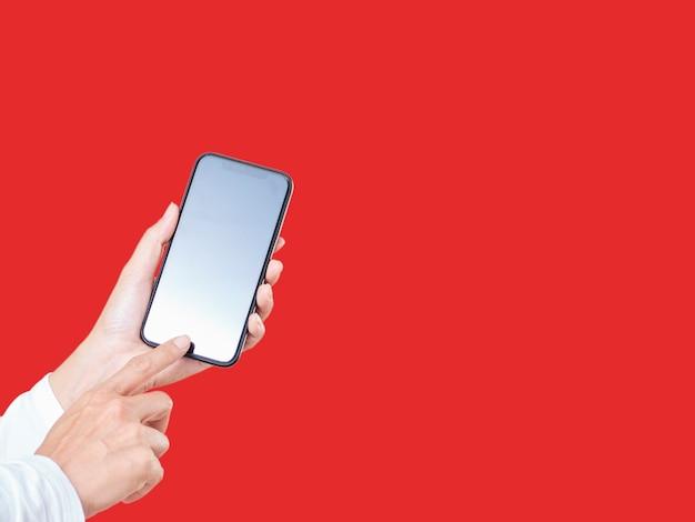 Zbliżenie dłoni kobiety dotykając wyświetlacz smartphone biały na białym tle na czerwonym tle