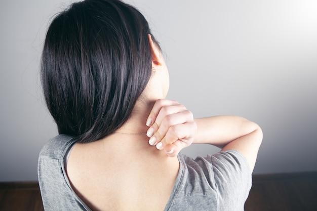 Zbliżenie dłoni kobiety masującej szyję. szyja dziewczyny boli