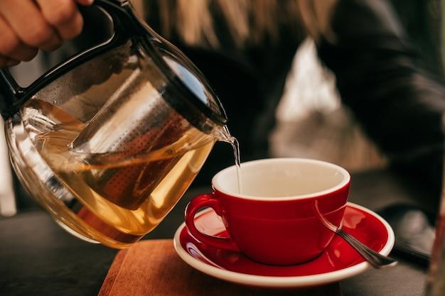 Zbliżenie dłoni kobiety nalewającej herbatę z czajnika do filiżanki