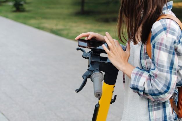 Zbliżenie dłoni kobiety płacącej za skuter elektryczny za pomocą aplikacji na telefon