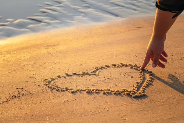 Zbliżenie dłoni kobiety rysunek serce z palcem na piasku na plaży.