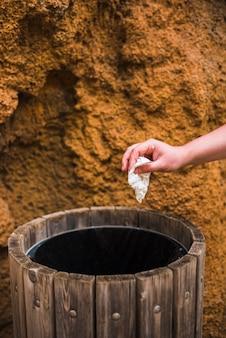 Zbliżenie dłoni kobiety rzucając biały papier w drewniane śmieci