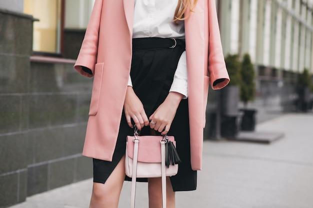 Zbliżenie dłoni kobiety spaceru ulicą miasta w różowym płaszczu