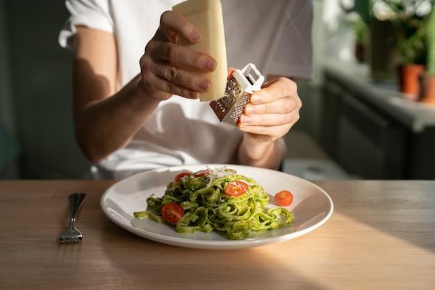 Zbliżenie dłoni kobiety tarcie parmezan w makaron z sosem pesto, świeże pomidory czereśniowe.