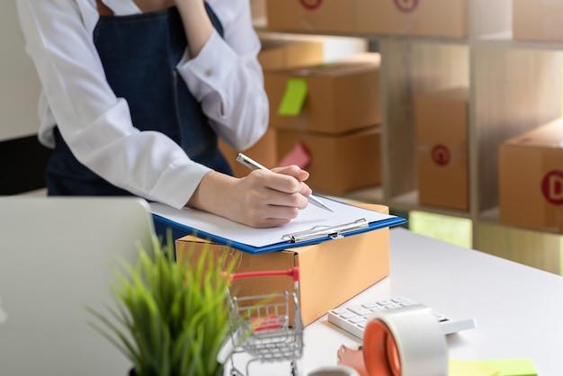 Zbliżenie dłoni kobiety trzymającej pióro i przyjmującej zamówienia ze sprzedaży online w domu.