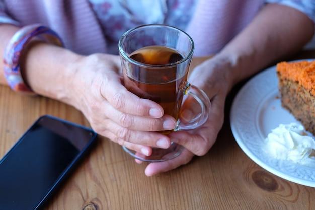 Zbliżenie dłoni kobiety w kawiarni, cieszącej się filiżanką herbaty i ciastem marchewkowym