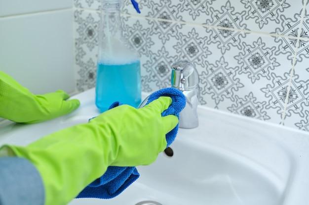 Zbliżenie dłoni kobiety w rękawiczkach z detergentem do mycia, czyszczenia i polerowania umywalki