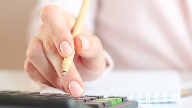 Zbliżenie dłoni kobiety z kalkulatorem liczenia i robienia notatek do notatnika. finanse, ekonomia, koncepcja technologii. różowe tło. selektywna ostrość.