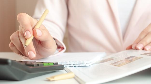 Zbliżenie dłoni kobiety z kalkulatorem liczenia i robienia notatek do notatnika.