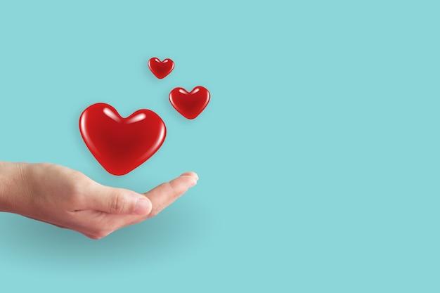 Zbliżenie dłoni kobiety z sercem z czystym pastelem. walentynki koncepcja miłości i opieki.