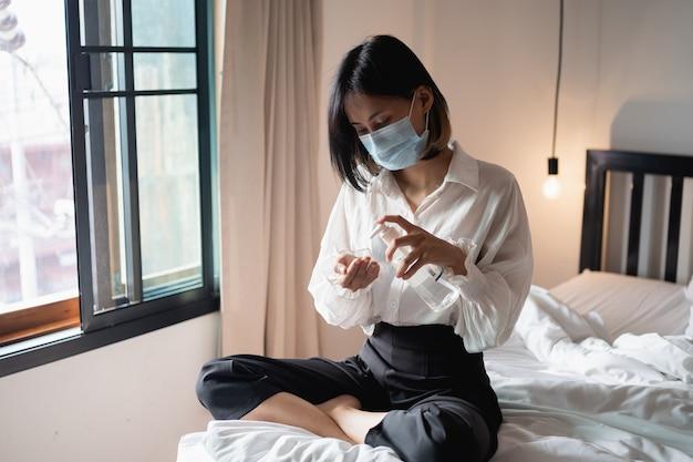 Zbliżenie dłoni kobiety za pomocą dozownika żelu do dezynfekcji rąk, przeciwko 2019-ncov w domu.