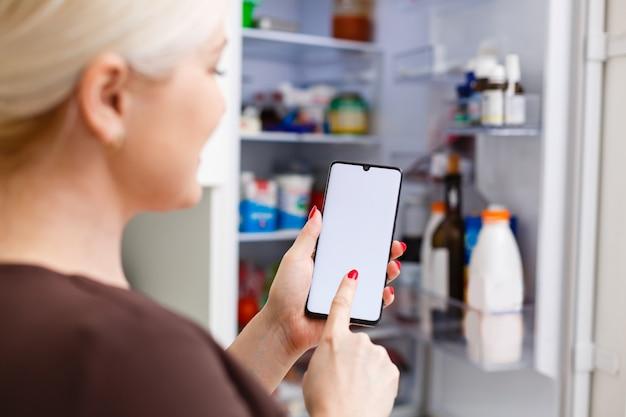 Zbliżenie dłoni kobiety za pomocą etykiety energetycznej na telefonie komórkowym przed lodówką w domu