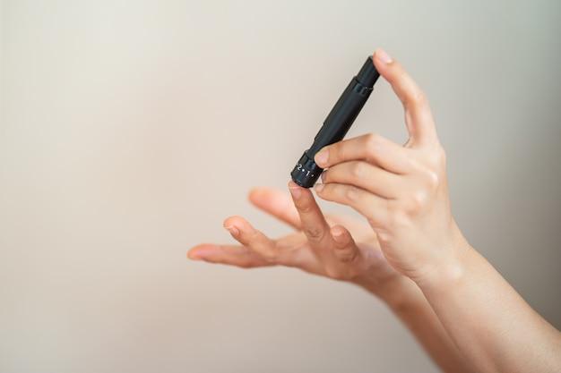 Zbliżenie dłoni kobiety za pomocą lancetu na palcu, aby sprawdzić poziom cukru we krwi przez glukometr. użyj jako koncepcji medycyny, cukrzycy, glikemii, opieki zdrowotnej i ludzi.
