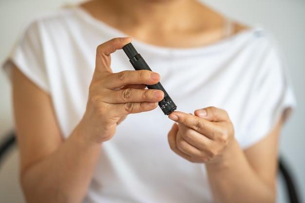 Zbliżenie dłoni kobiety za pomocą lancetu na palcu, aby sprawdzić poziom cukru we krwi przez glukometr.