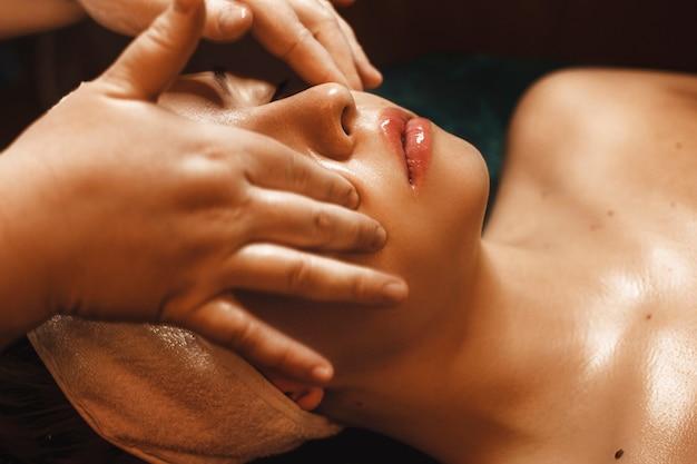Zbliżenie dłoni kosmetologa robi masaż twarzy kwasem hialuronowym kobiecie.